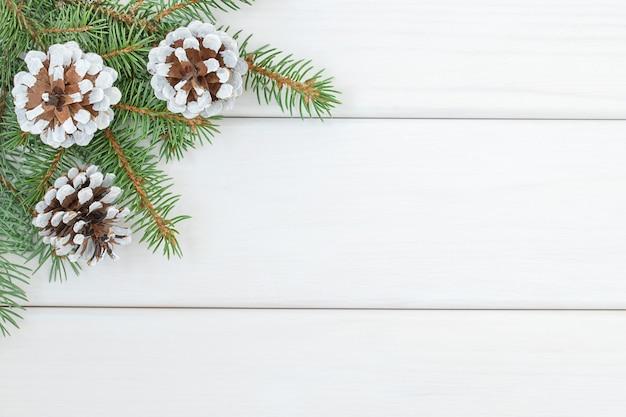 クリスマスツリーの枝とコーンとクリスマスの白い木製の背景