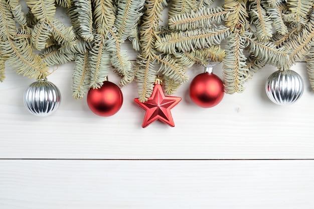 クリスマスツリーの枝やおもちゃとクリスマスの白い木製の模様のスペース