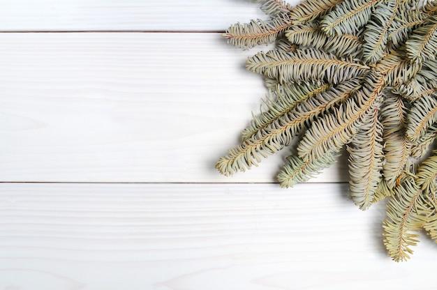クリスマスツリーの枝やおもちゃとクリスマスの白い木製の模様の表面 Premium写真