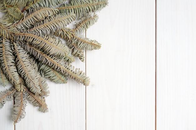 クリスマスツリーの枝とクリスマスの白い木製の模様の表面