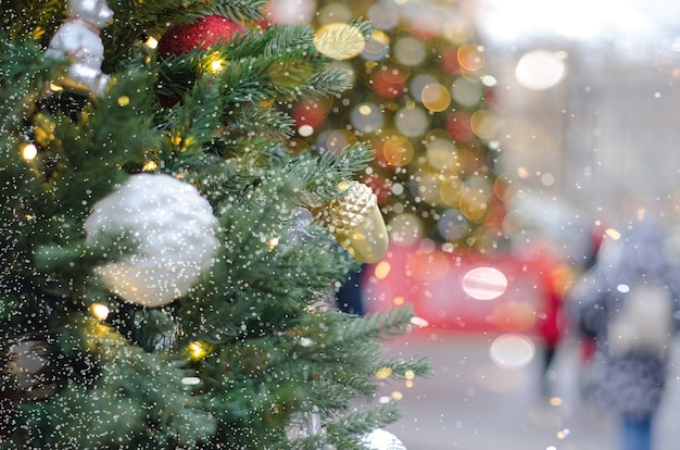 Christmas winter background. branches of the christmas tree on the street with snow and bokeh, selective blurry focus