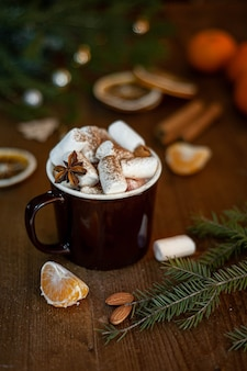 Christmas winter cocoa with marshmallow and lollipop in the shape of a christmas tree in a brown cup on a wooden background.