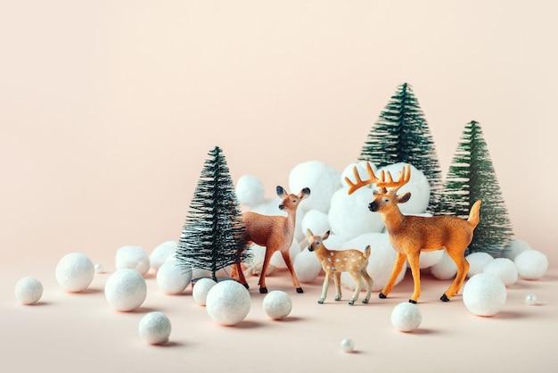 Новогодняя, зимняя композиция: семья оленей в зимнем лесу. счастливого рождества и нового года концепции. канун рождества