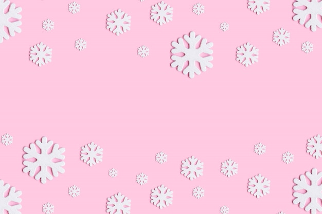 Christmas or winter composition. pattern made of snowflakes on pastel pink background.