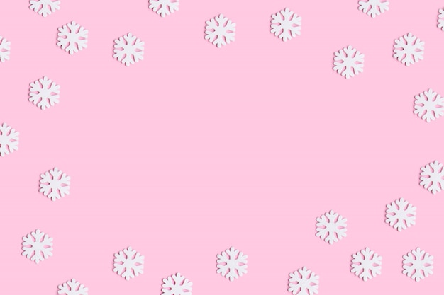 Christmas or winter composition of snowflakes on pastel pink background.