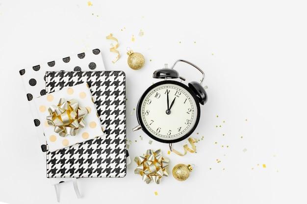 크리스마스 겨울 장식, 알람 시계가 있는 비즈니스 노트, 흰색 바탕에 비밀 산타의 선물. 사무실 축 하 개념입니다. 평평한 평지, 평면도