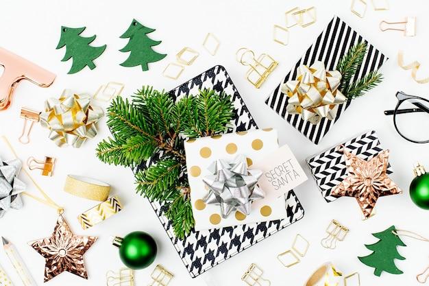 クリスマスの冬の装飾、ビジネスの文房具、白い背景の上の秘密のサンタからの贈り物。オフィスのお祝いのコンセプト。フラットレイ、上面図