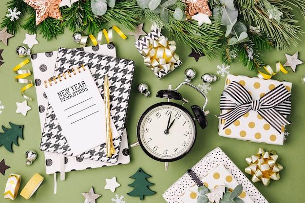 クリスマスの冬の装飾、目覚まし時計付きのノートブック、緑の背景にギフト。フラットレイ、上面図