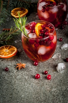 Christmas winter drinks. cold cocktail with cranberries, orange, rosemary, with spices (cinnamon, anise) and ice, on a dark stone table, copyspace