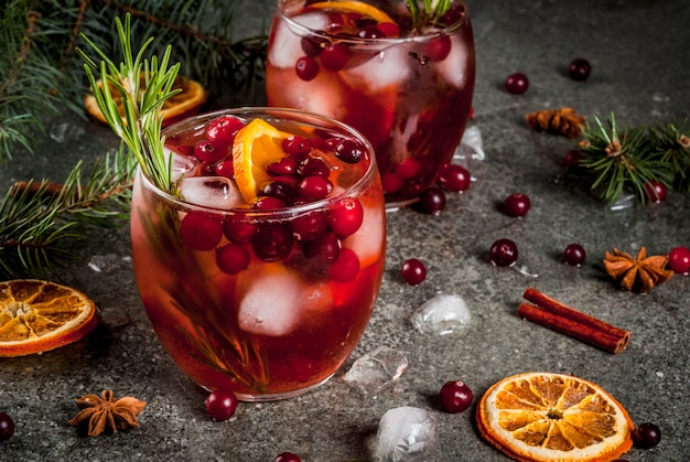 Christmas winter drinks cold cocktail with cranberries orange rosemary with spices (cinnamon anise) and ice on a dark stone table