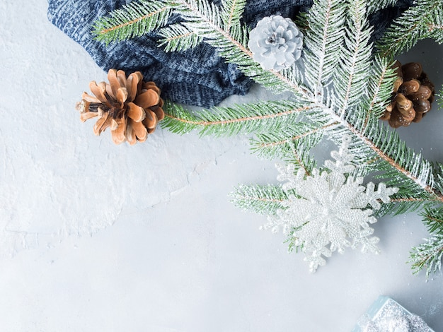 Christmas winter gray background with fir tree branches, pine cones, baubles and snow.