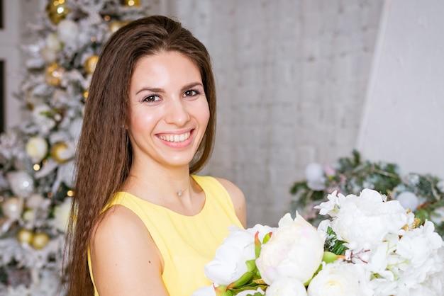クリスマス冬の休日のコンセプト黄色のドレスを着た美しい魅力的な女性が豪華なアパートでポーズをとる...
