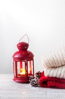 Natale o inverno concetto di casa con lanterna, pigne, neve e abbigliamento caldo, con spazio di copia