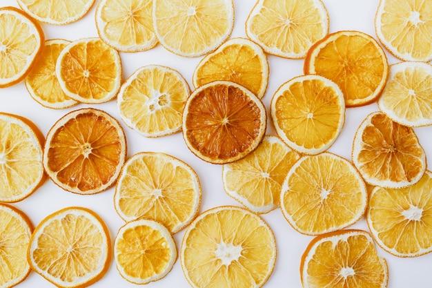 크리스마스, 겨울, 새해 구성입니다. 흰색 바탕에 마른 오렌지 조각입니다. 천연 감귤류 패턴입니다. 음식 배경입니다. 평평한 평지, 평면도.