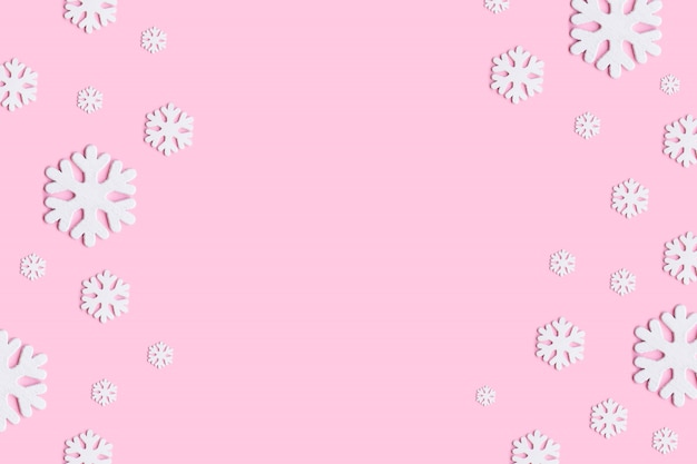 Christmas, winter, new year concept. winter composition of snowflakes on pastel pink background.