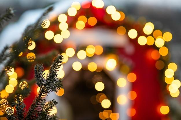 木々とお祝いのボケ味の照明とクリスマスの冬の通り