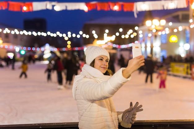 クリスマス、冬、テクノロジー、レジャーのコンセプト-屋外のアイススケートリンクでスマートフォンで写真を撮る幸せな若い女性。