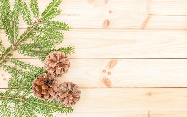 クリスマスツリーの枝とコーンとクリスマス冬の木製の背景