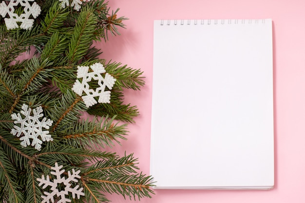 Christmas wish list on pink with fir branches and snowflakes, copyspace