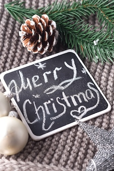 Christmas wishes written in chalk on a blackboard - happy christmas on warm scarf and toys