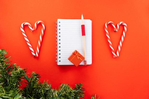 クリスマスのウィッシュリスト。クリスマス作曲。ギフトボックス、モミの木の枝、クリスマスキャンディー、赤い背景に赤いお祭りの装飾。スペースをコピーします。