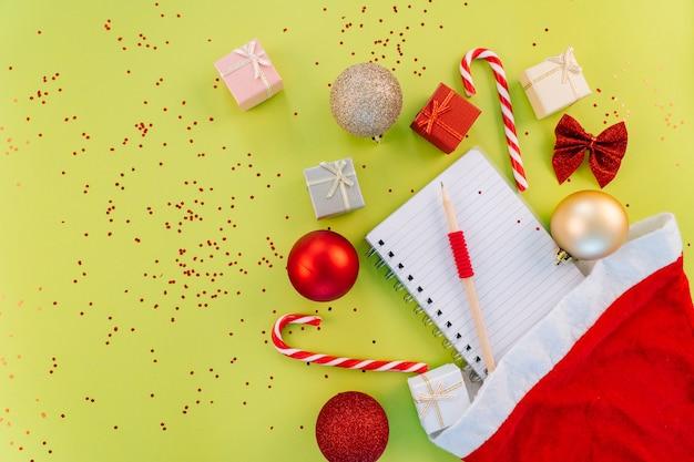 クリスマスのウィッシュリスト。クリスマス作曲。プレゼントボックス、クリスマスキャンディー、緑の背景に赤いお祭りの装飾。スペースをコピーします。