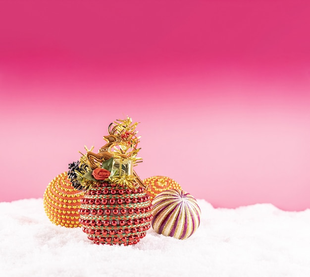 Christmas with colorful toys on snow on a pink background