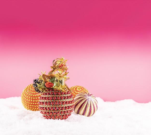 Natale con giocattoli colorati sulla neve su uno sfondo rosa