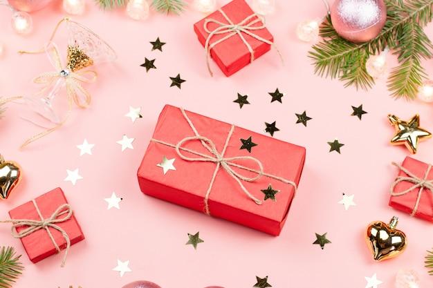 Рождество с еловыми ветками, красными подарочными коробками, золотыми украшениями на розовом.