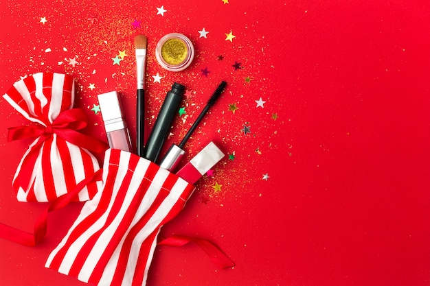 Christmas  with mascara, lipstick and shadows. flat lay composition with sparkles, gift bags and cosmetic products for the new year party.