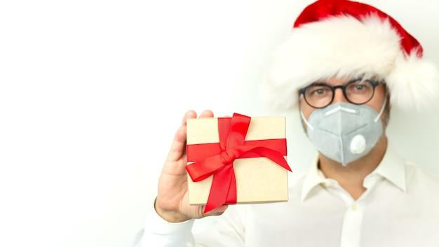 Рождество с концепцией карантина и социальной дистанции, мужчина в рождественской шляпе и держит подарочную коробку