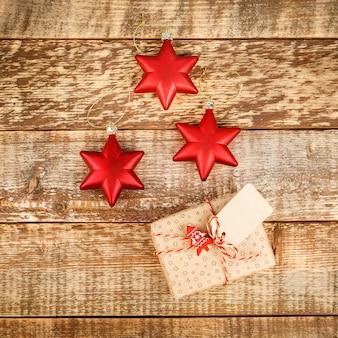 赤い装飾の星とボールと木の板のギフトボックスとクリスマス