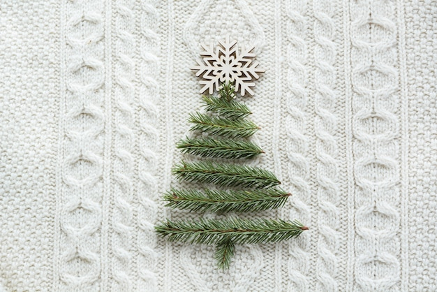 Christmas  with spruce, fir-tree, snowflakes, on white knitted background. holiday card. vintage style.