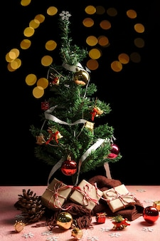 Рождество с рождественской елкой и сверкающими огнями боке на розовом.