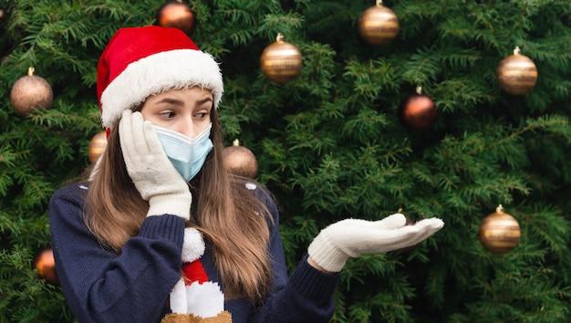 Рождество без подарка. крупным планом портрет женщины в шляпе санта-клауса и медицинской маске с эмоциями. на фоне елки. коронавирус пандемия