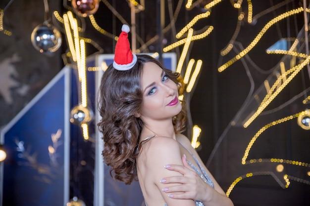 クリスマスの女性。赤い唇と驚いた表情でカメラを探しているマニキュアのサンタクロースの帽子の美少女モデル。クローズアップの肖像画。感情。新年セールを楽しんでいます。クリスマスの女性。