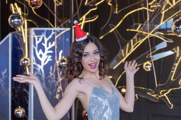 クリスマスの女性。赤い唇と驚いた表情でカメラを探しているマニキュアのサンタクロースの帽子の美少女モデル。クローズアップの肖像画。感情。新年セール、冬休みを楽しむ