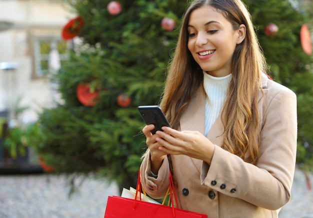 Christmas woman buying online on the smart phone in the street with christmas tree on background.