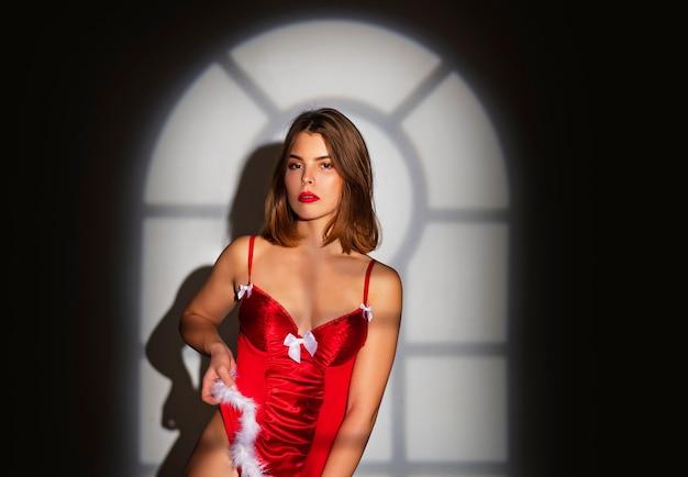 クリスマスの女性のドレス。クリスマスツリーと屋内でモデルの女の子のファッションの肖像画。