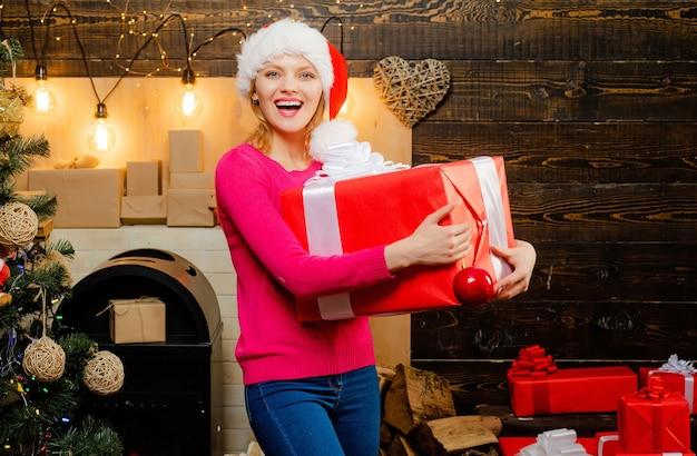 クリスマスの女性のドレス。ヴィンテージの木製の背景にポーズをとってセクシーなサンタの女性。お正月の女の子。可愛い