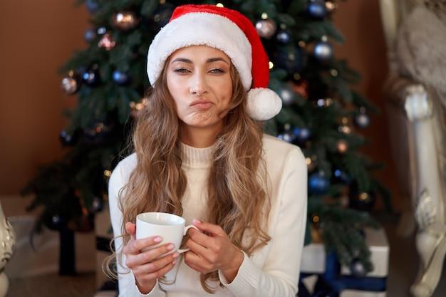 크리스마스. 여자 옷을 입고 흰색 스웨터 산타 모자와 청바지 선물 상자와 함께 크리스마스 트리 근처 바닥에 앉아