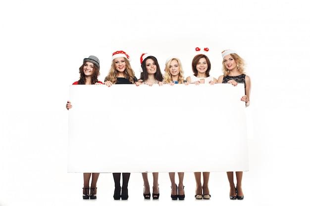 クリスマスの女性は大きな白いカードを保持します。サンタ帽子。孤立した笑顔の女の子。