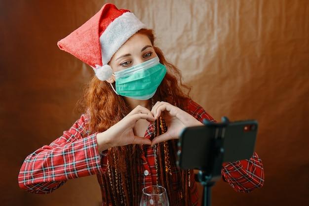 ハートの形に手を組んでスマートフォンのウェブカメラを使用してオンラインビデオ通話を行う医療マスクのクリスマスの女性。サンタの帽子と市松模様のパジャマを着た女性。検疫の年末年始。