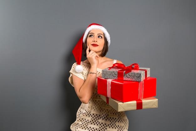 クリスマスの女性は空のコピースペースを検索ギフトボックスプレゼントを保持し、若い幸せな笑顔の女性はサンタクロースの帽子をかぶって、魅力的な新年のパーティーの女の子、