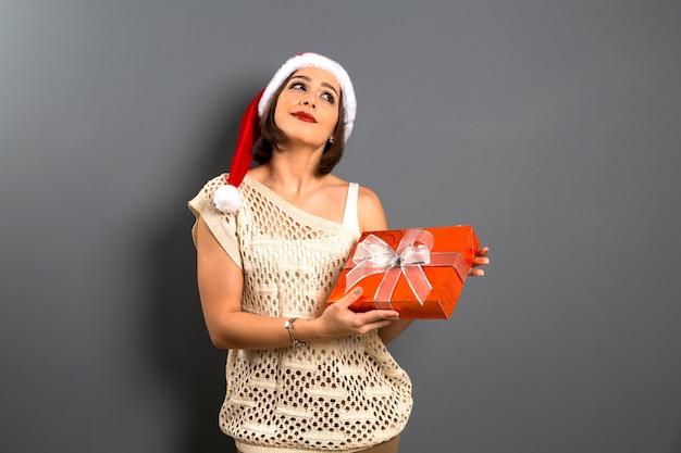 크리스마스 여자 조회 빈 복사본 공간 보류 선물 상자 선물, 젊은 행복 미소 여자 산타 클로스 모자를 착용, 매력적인 새해 파티 소녀,