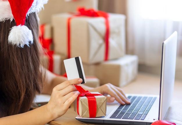 인터넷 쇼핑을 하는 노트북에 크리스마스 여자 온라인으로 선물을 사거나 무언가를 얻는 여자