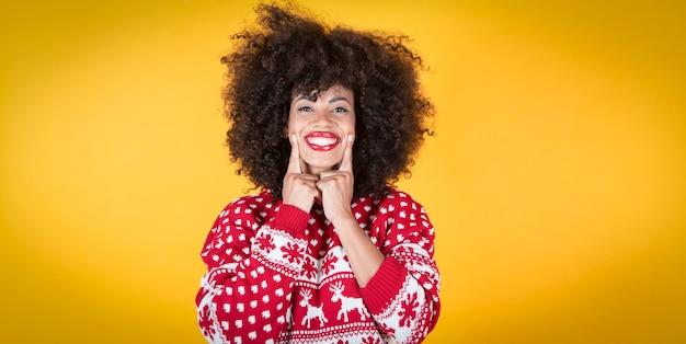 彼女の笑顔の黄色の背景を指すクリスマスの女性