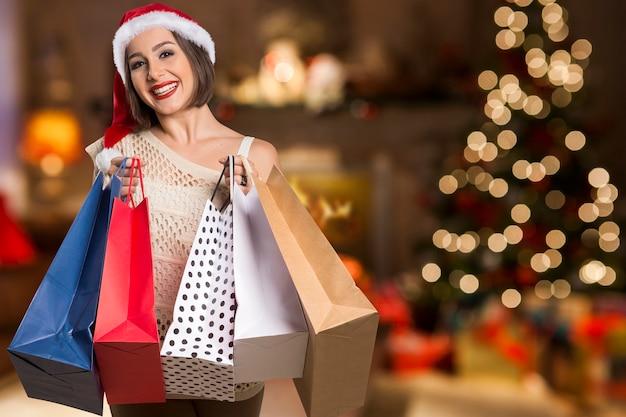Christmas woman portrait hold shopping bags. smiling happy woman over bokeh christmas lights