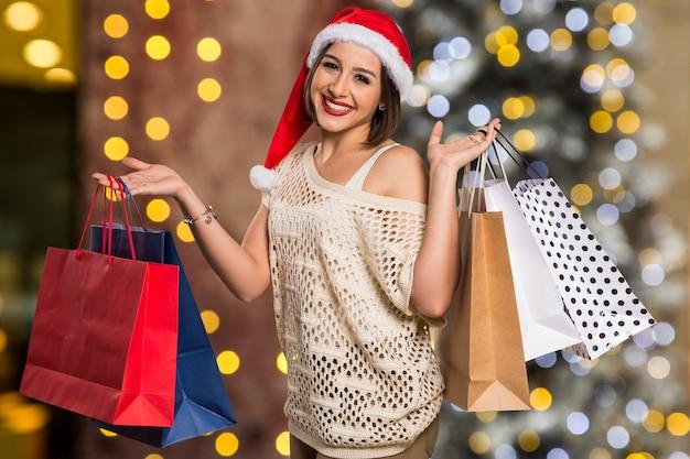 Рождественский женский портрет, держащий рождественский подарок. улыбается счастливая женщина над боке рождественские огни