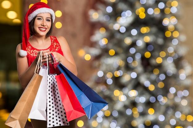 Christmas woman portrait holding shopping bags. smiling happy woman over bokeh christmas lights